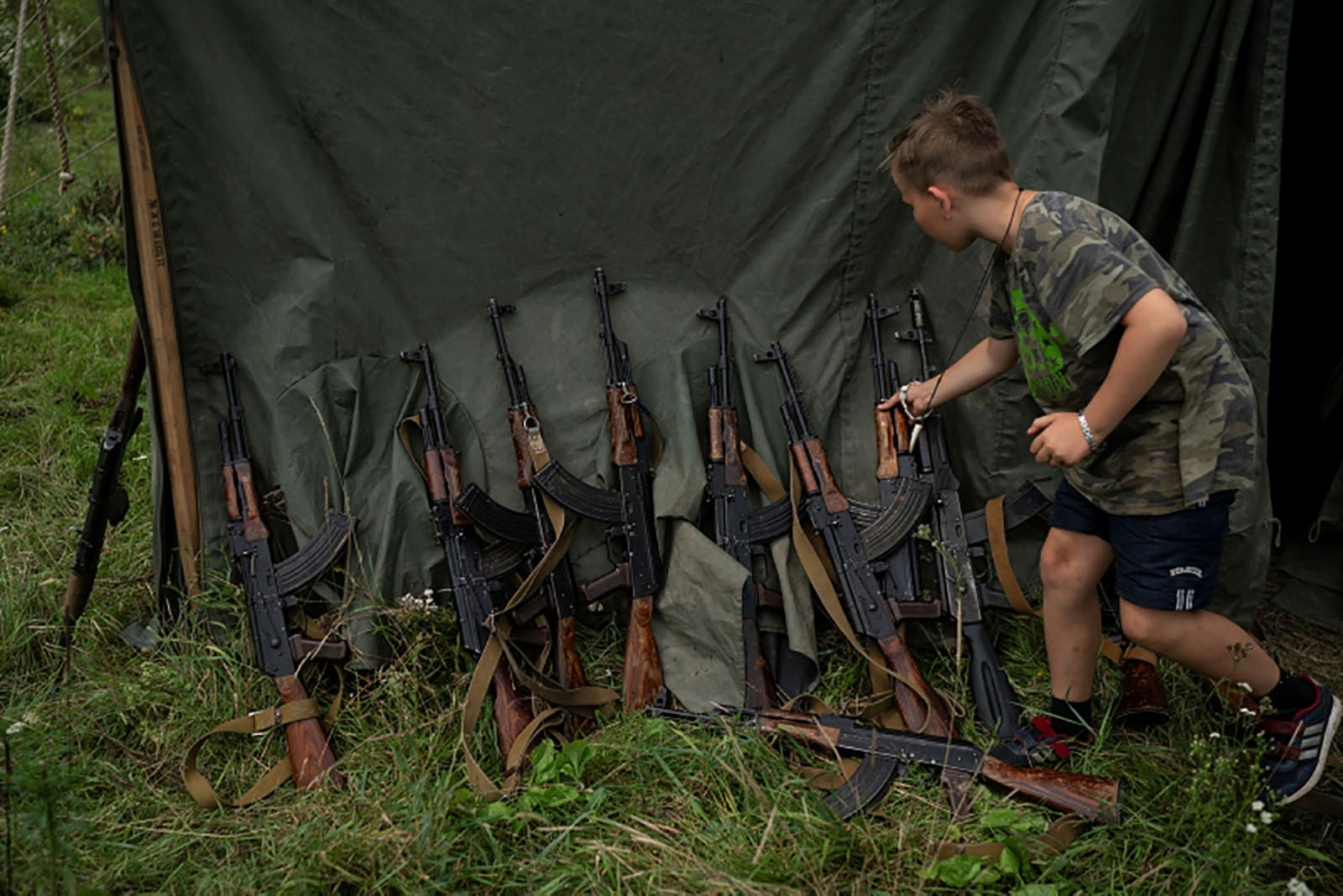 A young of the camp grabs his AK-47 during a tactical exercise.