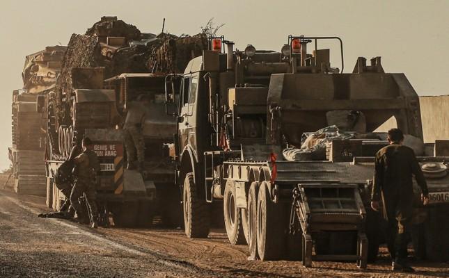 Turkish soldiers work on uploading tanks from trucks on a road towards the border of Syria in Şanlıurfa province, Turkey, Monday, Oct. 14, 2019. AP Photo