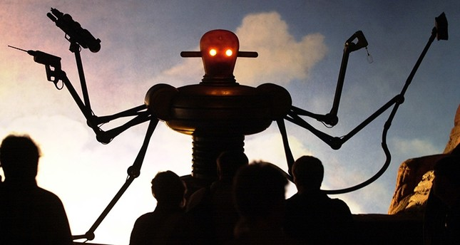 In this Tuesday, Aug. 1, 2000 file photo, visitors of the world exhibition Expo 2000 stand in front of a robot display at the Planet of Visions exhibit at the Expoground in Hanover, northern Germany. (AP Photo)