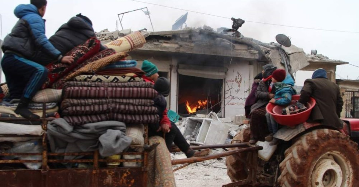 Displaced Syrians pass a house still on fire as they flee shelling on the town of Abyan, in the western rebel-held part of the northern Syrian province of Aleppo, near the border with Turkey, Feb. 13, 2020.  (AFP)