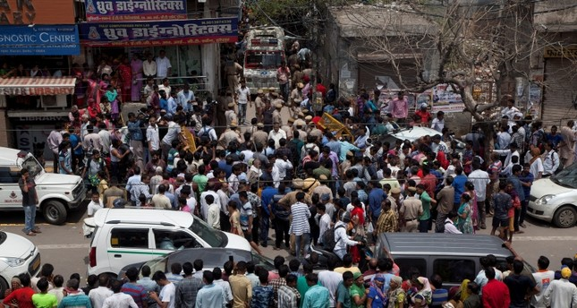 Pedestrians gather near the house where Indian police found 11 bodies in Burari village, north Delhi, India, Sunday, July 1, 2018. (AP Photo)