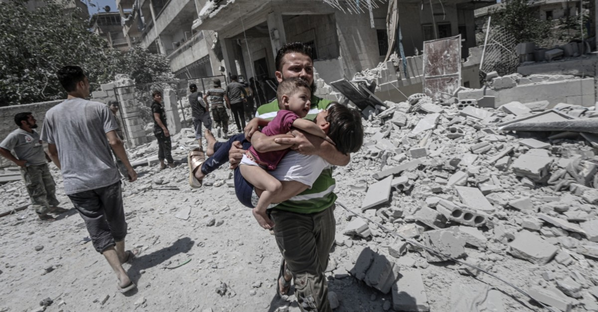 A man carries away two children following a regime attack in Idlib, July 24, 2019.