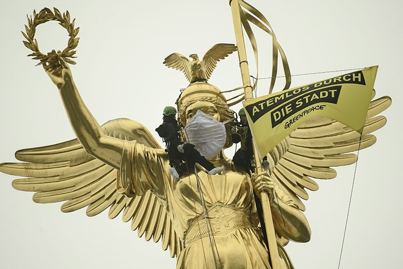 Activists of the environmental protection organization 'Greenpeace' put a oversized protection mask on the face of the bronze sculpture of the Victoria on top of the Victory Column in Berlin, Germany. Jan. 2017. (EPA File Photo)