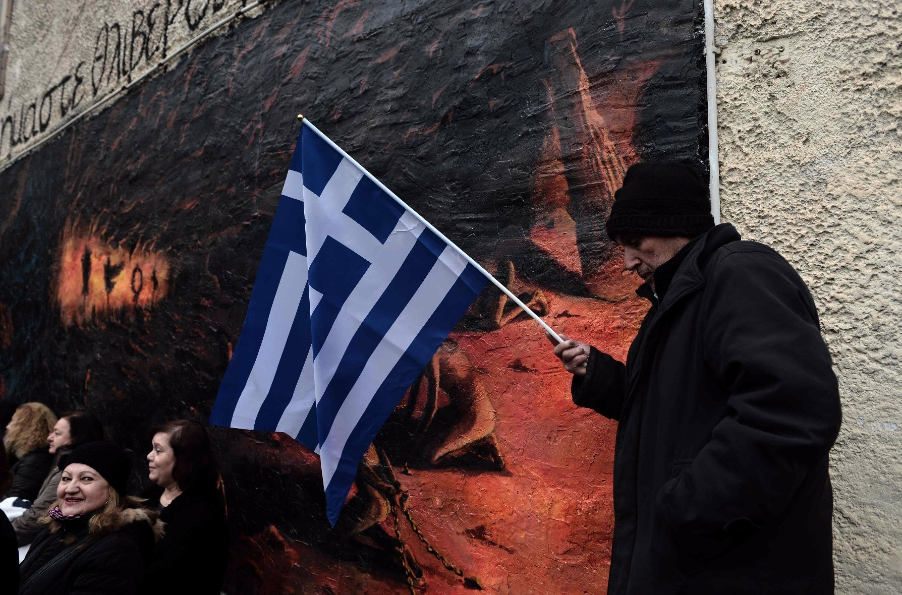 A man holds a Greek national flag as he takes part in a demonstration against the Prespa agreement, Veria, Jan. 22, 2019.