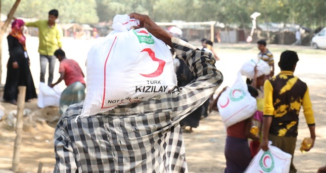 A Rohingya man carries an aid pack donated by Red Crescent.