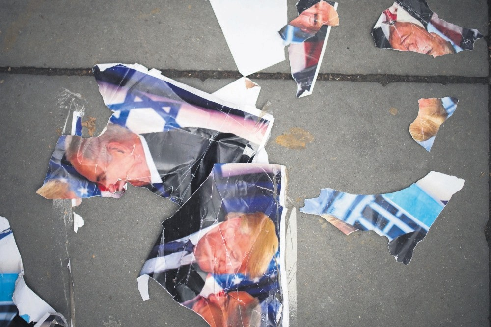 A ripped poster of U.S. President Trump and Israeli PM Netanyahu on the ground during a protest against Trump's decision to recognize Jerusalem as Israel's capital, Paris, Dec. 9.