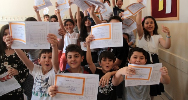Young students at a school in the eastern city of Elazığ show their report cards.
