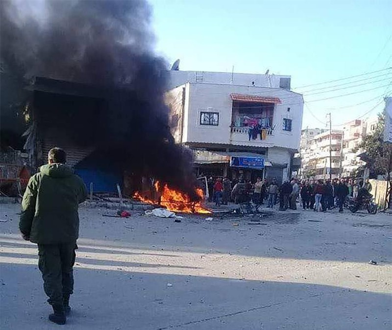 This handout image made available by the official Syrian Arab News Agency (SANA)'s Telegram page on January 22, 2019, shows people gathering around a burning vehicle in the Syrian regime's coastal stronghold of Latakia. (AFP Photo)