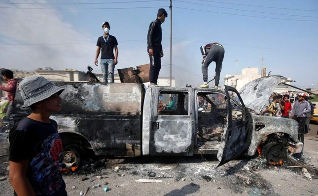 Protesters stand on a military vehicle belonging to the Iraqi security forces after burning it, Basra, Nov. 24, 2019. (REUTERS Photo)