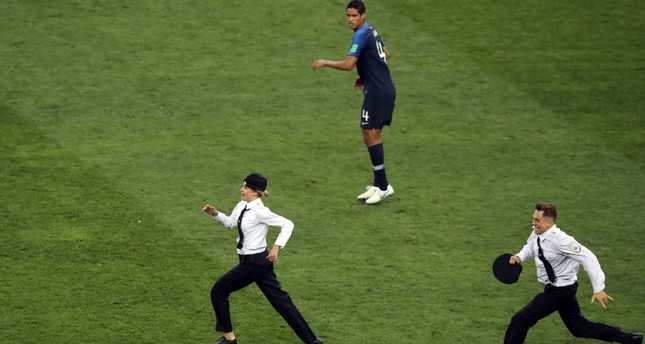 France's Raphael Varane, top, and France's Samuel Umtiti look at two people that invaded the pitch during the final match between France and Croatia at the 2018 World Cup in Moscow, Russia, Sunday, July 15, 2018. (AP Photo)