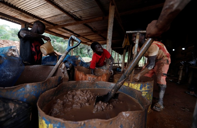 A young artisanal miner washes crushed rock containing gold in metal drums at the unlicensed mining site of Nsuaem Top in Ghana, November 23, 2018.
