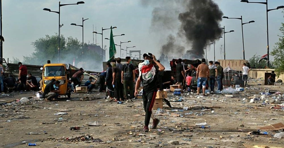 Anti-government protesters set a fire while Iraqi security forces close the bridge leading to the Green Zone, Baghdad, Oct. 27, 2019. (AP Photo)