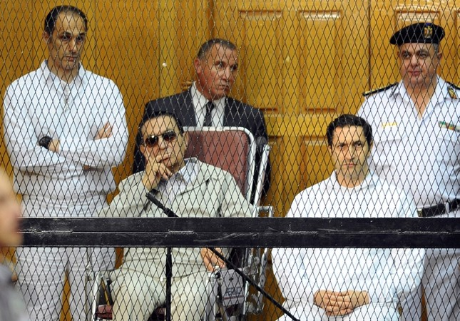 In this Sept. 14, 2013 file photo, former Egyptian President Hosni Mubarak, seated center left, and his two sons, Gamal Mubarak, left, and Alaa Mubarak attend a hearing in a courtroom in Cairo, Egypt. (AP Photo)