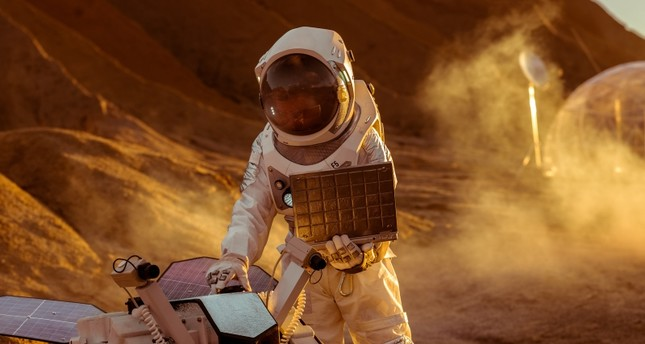 Astronaut in a space suit works on laptop, adjusting rover for Mars. (GETTY IMAGES/ iStock Photo)
