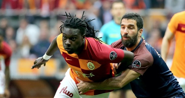 Galatasaray's Bafetimbi Gomis (L) and Medipol Başakşehir's Arda Turan vie for ball during the match at Türk Telekom Arena, Istanbul.