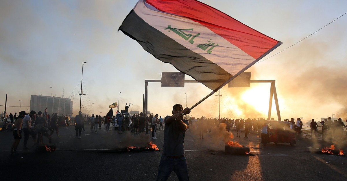 An Iraqi protester waves the national flag during a demonstration against the government, in the Iraqi capital Baghdad, Oct. 5, 2019.