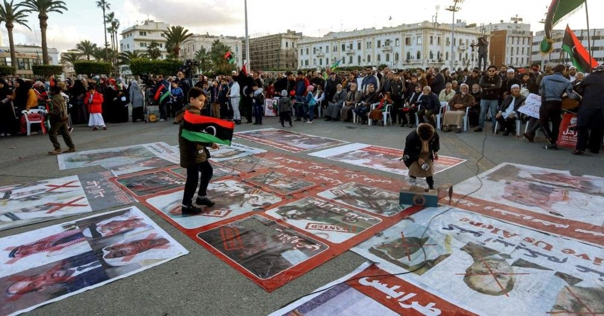 Portraits of Egyptian President Abdel Fattah al-Sisi, Saudi King Salman bin Abdulaziz, and Abu Dhabi Crown Prince Mohammed bin Zayed are displayed on the ground covered with red cross marks as people demonstrate against them and against eastern Libyan strongman Khalifa Haftar, and in support of the UN-recognized GNA in the Martyrs' Square in Tripoli, Dec. 27, 2019 (AFP Photo)