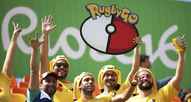"""Rugby fans dressed as Pikachu from """"Pokemon Go"""" watch from the stands."""