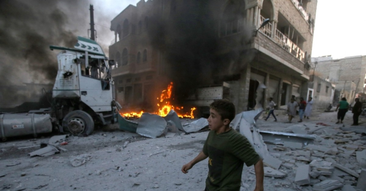 A young boy runs past a fire started in a building following a reported airstrike by Assad regime forces in the town of Maaret al-Numan in Syria's northwestern Idlib province on August 28, 2019. (AFP Photo)