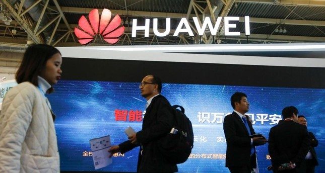 People walk past the stall of Huawei Technologies at the Security China 2018 exhibition on public safety and security in Beijing, Oct. 23.