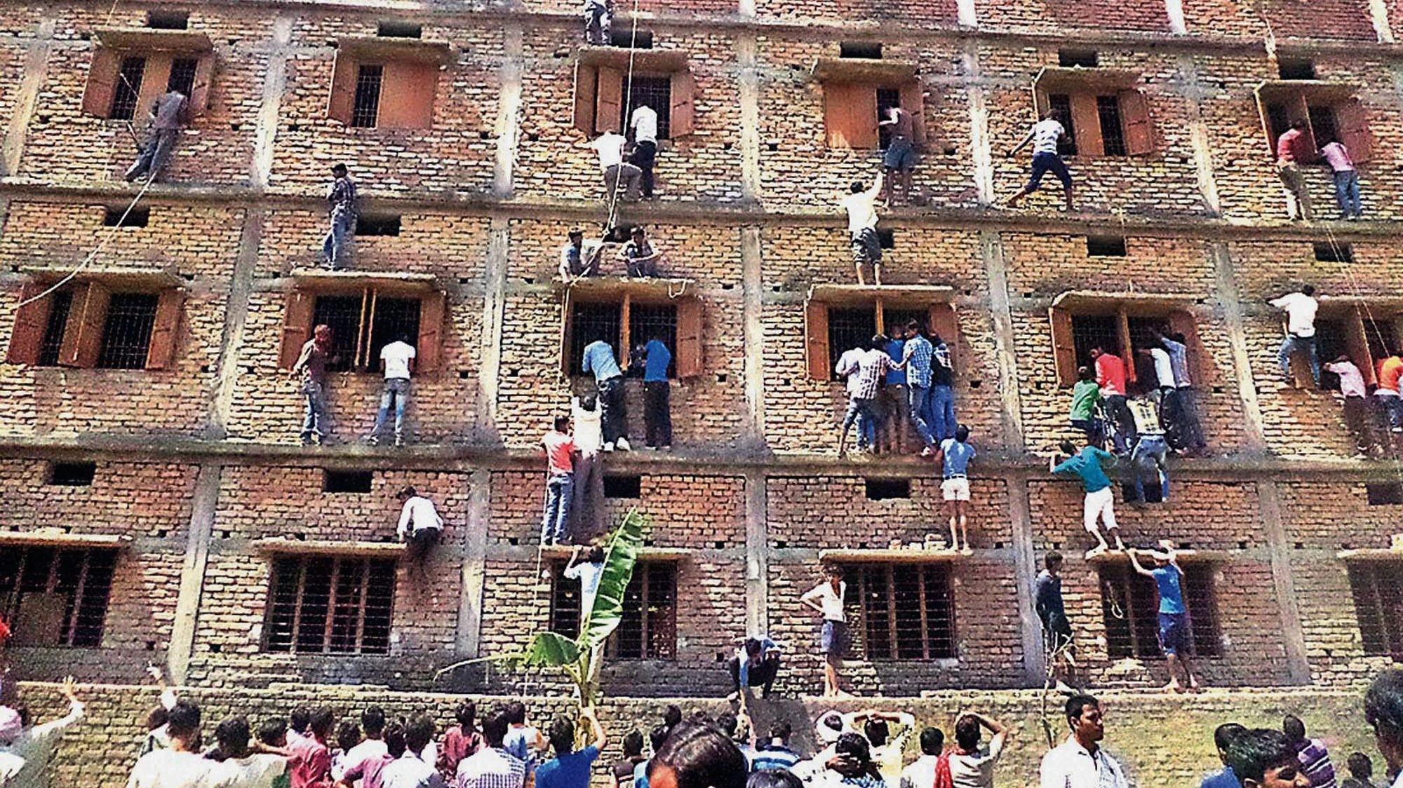 In this March 2014 photo, Indians climb the wall of a building to help out students taking exams in Hajipur, Bihar. (AP Photo
