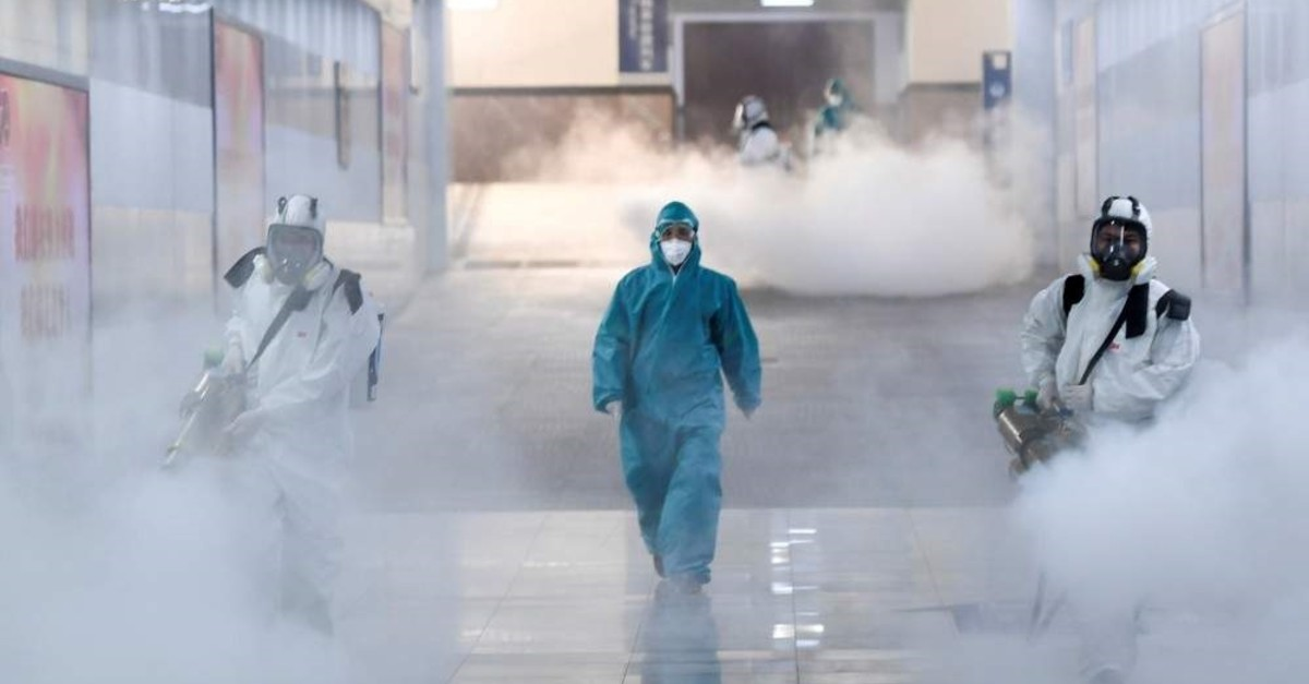 Volunteers in protective suits disinfect a railway station, Changsha, Feb. 4, 2020. (REUTERS Photo)