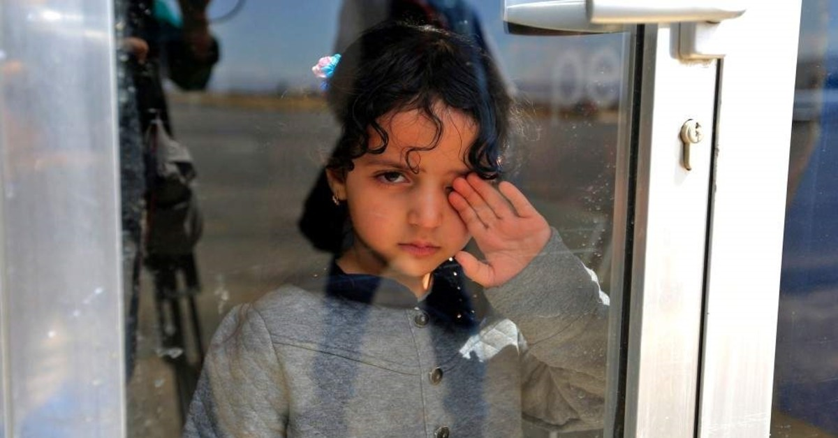 A Yemeni child patient looks through a glass door pane while awaiting at Sanaa International Airport on February 3, 2020, for evacuation aboard a U.N. aircraft bound for the Jordanian capital Amman to receive medical treatment there. (AFP Photo)