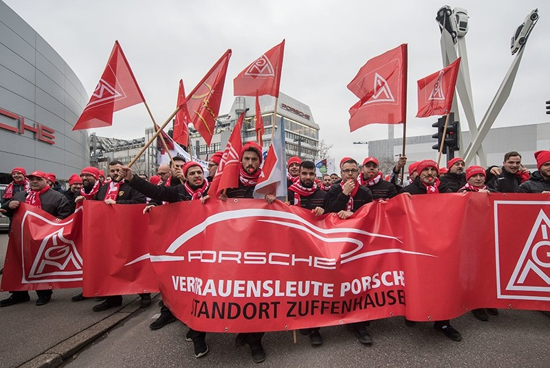 Employees of the Porsche AG company hold flags with the logo of Germany's metalworkers' union IG Metall as they demonstrate on January 8, 2018 in front of their plant in Stuttgart, southern Germany. (APF Photo)