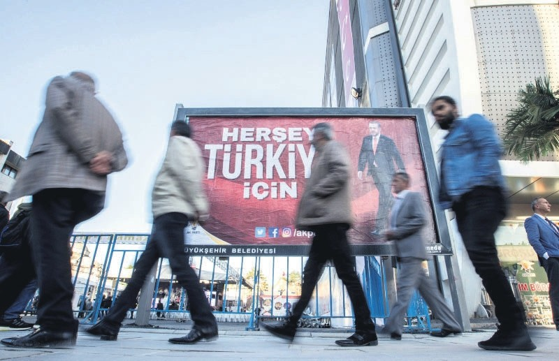 People walk in front of a billboard that reads ,Everything for Turkey, in Van province, eastern Turkey, May 16.