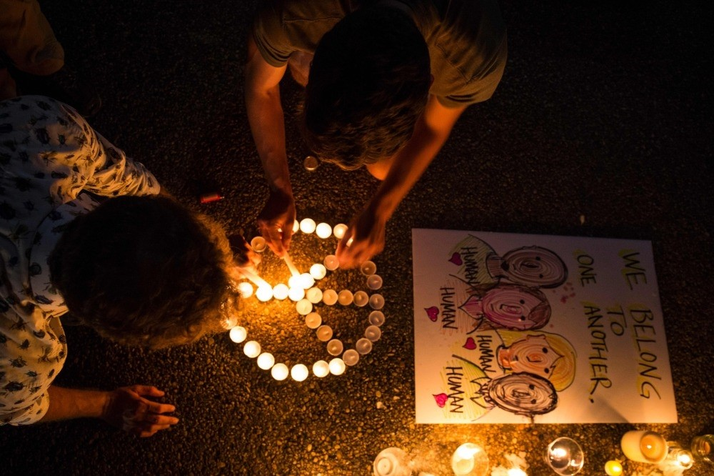 People light candles in the form of a peace sign in front of the White House at a vigil for a civilian killed by a white supremacist in Charlottesville, Virginia, Aug. 13.