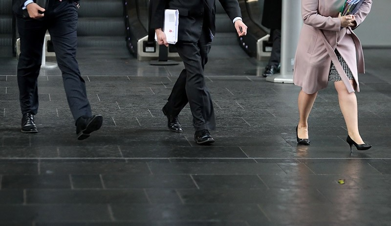 Business men and women walk in the City of London on April 4, 2018. (AFP Photo)