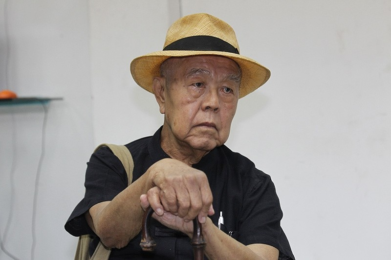 Thai social critic Sulak Sivaraksa sits at a police station before going to Bangkok military court in Bangkok, Thailand, Monday, Oct. 9, 2017. (AP Photo)