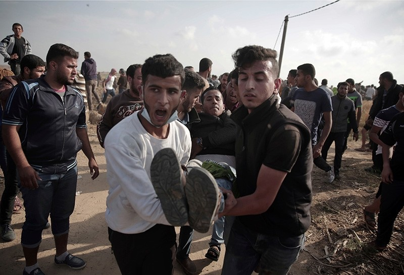 In this April 27, 2018, file photo, Palestinians carry a wounded man during a protest at the Gaza Strip's border with Israel. (AP Photo)