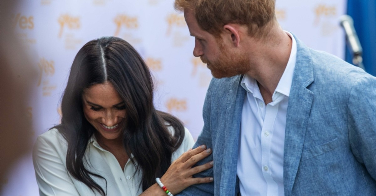 Britain's Prince Harry, Duke of Sussex(R) and Meghan, Duchess of Sussex(L) leave the Youth Employment Services Hub in Tembisa township, Johannesburg, on October 2, 2019. (AFP Photo)