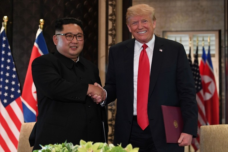 US President Donald Trump (R) and North Korea's leader Kim Jong Un shake hands following a signing ceremony during their historic US-North Korea summit, at the Capella Hotel on Sentosa island in Singapore on June 12, 2018. (AFP Photo)