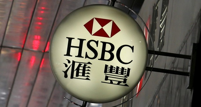 A man walks past a logo of HSBC outside a branch at the financial Central district in Hong Kong.