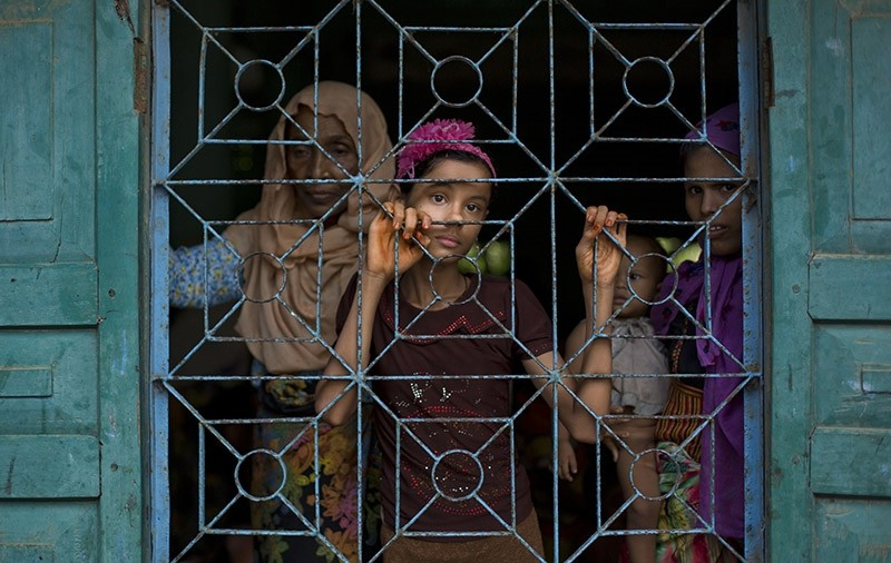Newly arrived Rohingya Muslims from Myanmar look out from a madrasa window that they used as a shelter in Shahparirdwip, Bangladesh, Monday, Oct. 2, 2017. (AP Photo)