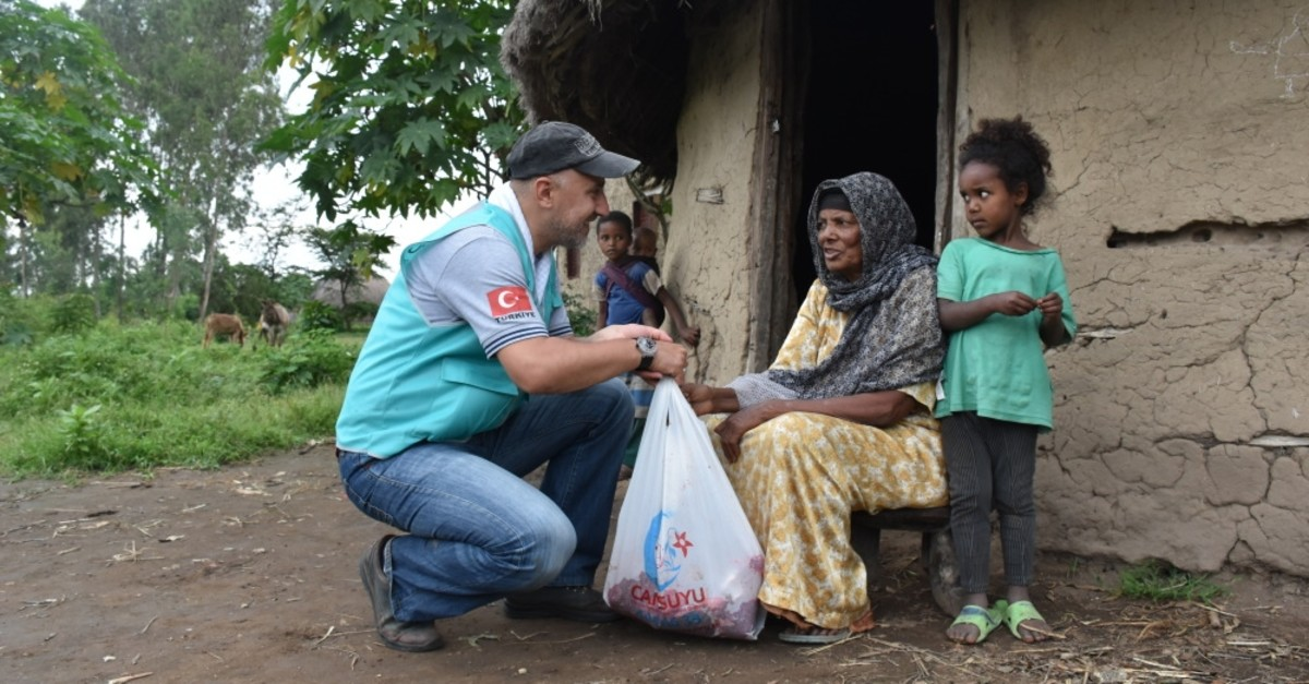 A volunteer from Turkish charity Cansuyu delivers food aid to a woman in a village in Ethiophia's Hadiya, Aug. 12, 2019.