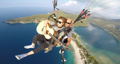 Multitasking at its best: Chinese artist plays guitar while paragliding in Fethiye