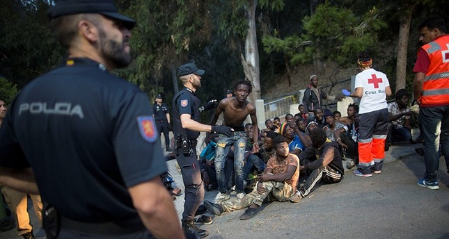 Police stand around a group of African migrants as Red Cross workers attend the injured after they crossed the border fence from Morocco to Spain's North African enclave of Ceuta, Spain August 1, 2017. (Reuters Photo)