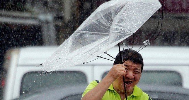 A Taiwanese man holds an umbrella against powerful gusts of wind generated by typhoon Lekima in Taipei, Taiwan, Friday, Aug. 9, 2019. AP Photo