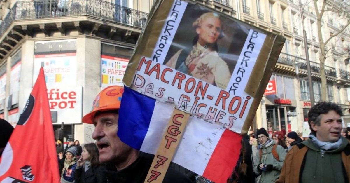 A protester hods a poster showing French President Emmanuel Macron as King Louis XVI during a demonstration, Paris, Jan. 24, 2020. (AP Photo)