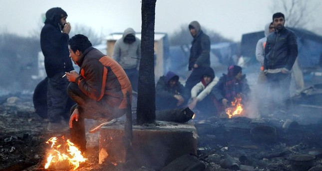 Migrants walking through a partially destroyed camp, during the dismantling of the makeshift shelter migrant camp dubbed the 'Jungle', in Calais, France.