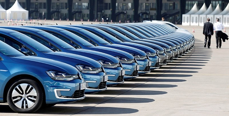People walk past a row of Volkswagen e-Golf cars during the company's annual news conference in Berlin, Germany March 13, 2014. (Reuters Photo)