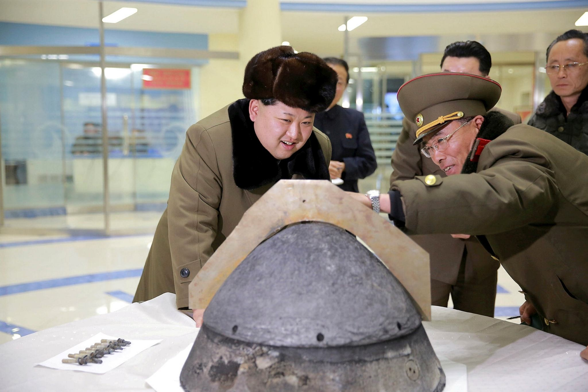 North Korean leader Kim Jong Un looks at a rocket warhead tip after a simulated test of atmospheric re-entry of a ballistic missile, at an unidentified location in this undated file photo released by North Korea's KCNA in Pyongyang on March 15, 2016.