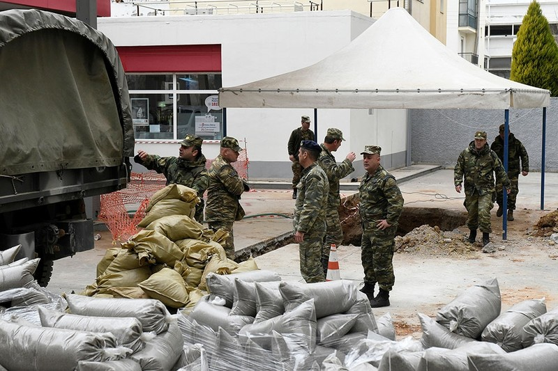 Military officers unload sacks of sand next to a hole in the ground (R), where a 250 kg World War Two bomb was found during excavation works at a gas station. (Reuters Photo)