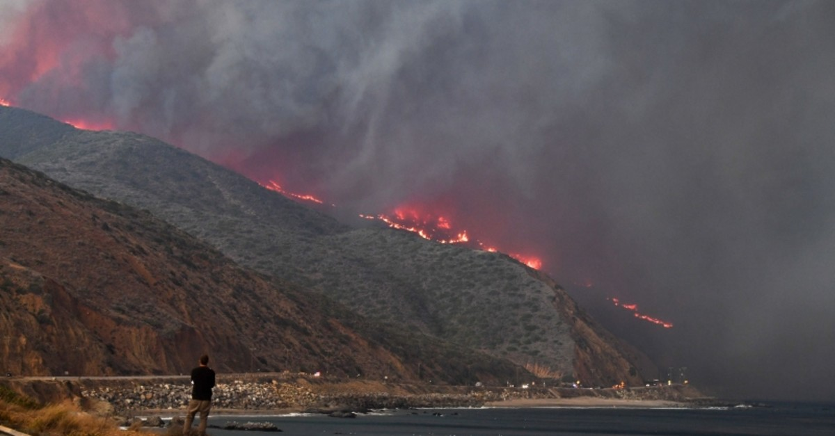 A man watches as the Woolsey Fire reaches the ocean along Pacific Coast Highway (Highway 1) near Malibu, California (AFP Photo)