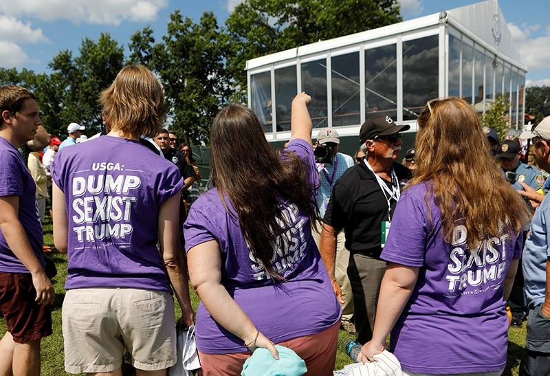 Protesters wearing anti-Trump shirts look up toward U.S. President Donald Trump's personal enclosure at the U.S. Women's Open golf tournament at Trump National Golf Club in Bedminster, New Jersey, U.S. July 16, 2017. (Reuters Photo)