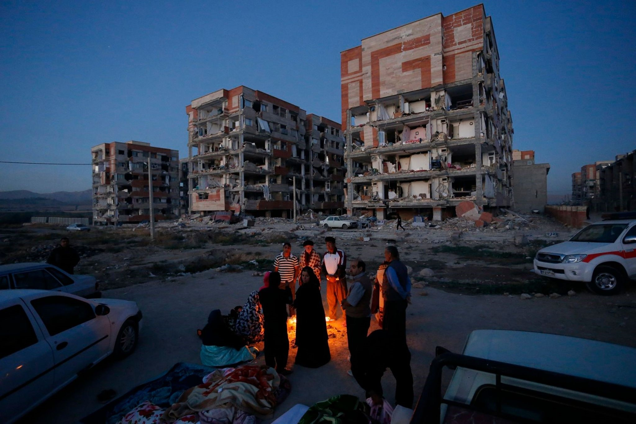 Residents huddle by a fire in an open area following a 7.3-magnitude earthquake in western Iran's Kermanshah province, Nov. 13.