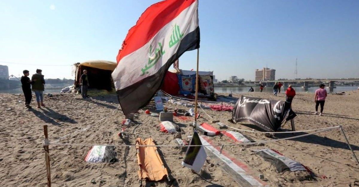 Iraqis pass by a symbolic cemetary for anti-government protesters who died in ongoing rallies, Baghdad, Dec. 21, 2019. (AFP Photo)